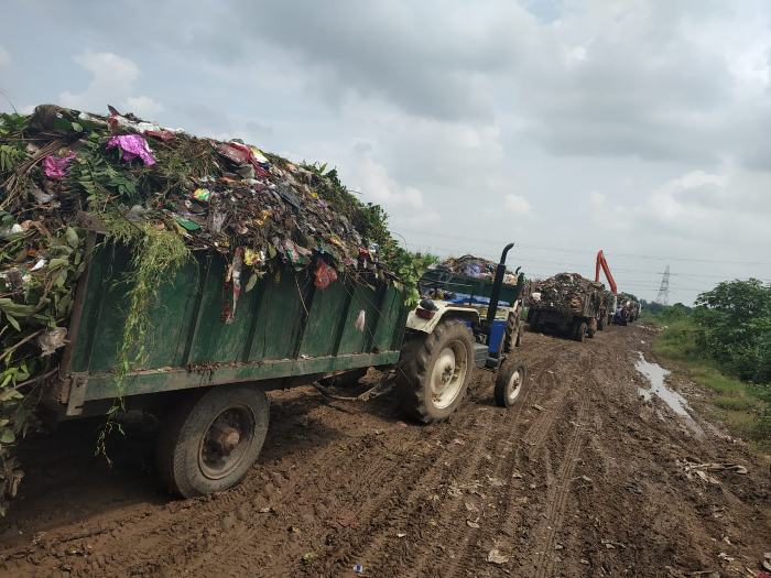 Open tractors transporting Meerut's mixed solid waste to Ganwri village for dumping